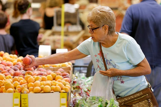 Delila Cooper of West Lafayette picks out a nectarine during the grand opening of the Fresh Thyme., 2410 N Salisbury st., Wednesday, June 26, 2019 in West Lafayette.
