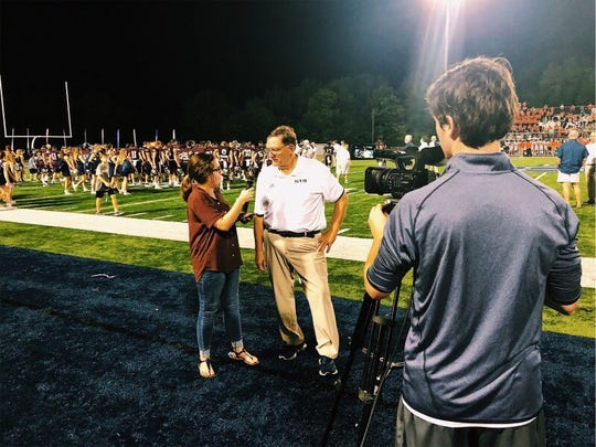 Carlin Sekhani-Matthews, a rising senior at St. Thomas More Catholic High School, conducts an interview on the sidelines of a football game.