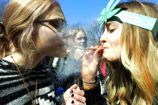 Participants take celebratory smoke April 4, 2015 during the annual Hash Bash at the University of Michigan in Ann Arbor. Michigan's liberal stance on marijuana has attracted out-of-state investors, industry experts say.
