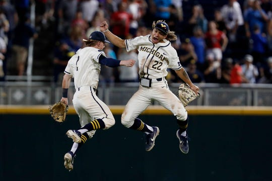 Michigan Wolverines center fielder Jesse Franklin (7) and Michigan Wolverines right fielder Jordan Brewer (22) celebrate after defeating Vanderbilt in Game 1 of College World Series.