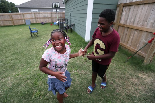 Dyiriun Hampton, 13, plays with his sister Zyiriana Coleman, 8, in the backyard of their new home on Tuesday, June 25, 2019. Jessica Wester, mother to the two children, was able to move them to the Oakhaven residence from North Memphis last November, in an effort to find a more stable and safer environment.