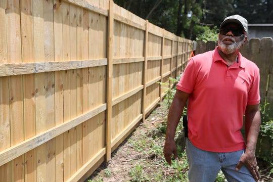Larry Donald, a retiree from the Christine Gardens subdivision, looks over a newly constructed fence at the property line between his neighborhood and Saia's planned 24-hour trucking terminal.