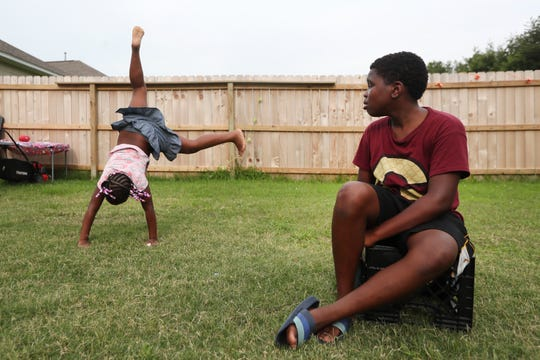 Zyiriana Coleman, 8, does a cartwheel while her brother Dyiriun Hampton, 13, watches in the backyard of their new home on Tuesday, June 25, 2019. Jessica Wester, mother to the two children, was able to move them to the Oakhaven residence from North Memphis last November, in an effort to find a more stable and safer environment.