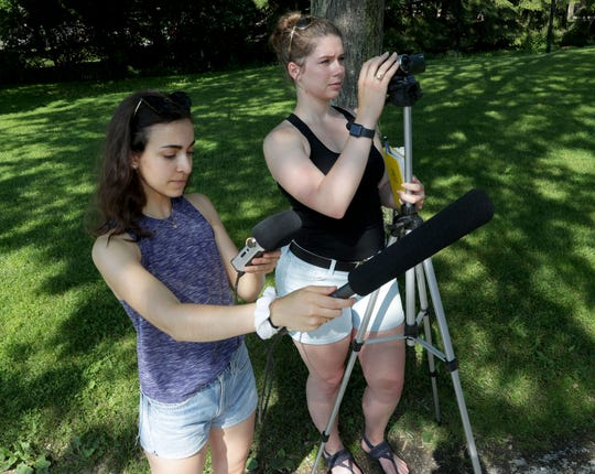 Carthage College students Azniv Khaligian (left) records audio as Joy Layton videotapes the gibbons at the zoo.