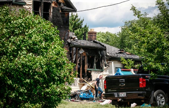 Greg Steenweg, Town of Langlade Fire Chief, clears debris Wednesday from the house destroyed by fire Tuesday in Pickerel, Wis.