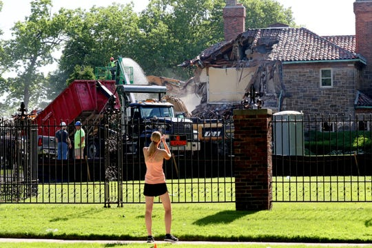 A woman stops to take a photo of the demolition of a historic Shorewood mansion. The property, owned by Milwaukee County Executive Chris Abele, will be the site of Abele's new home.