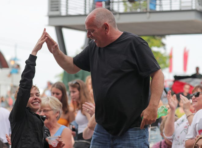 A couple high five as the The Big Bang Theory plays on the Briggs & Stratton Big Backyard stage at Summerfest in Milwaukee on Wednesday, June 26, 2019.