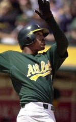Oakland Athletics' Terrence Long follows through on a three-run home run off Chicago White Sox's Mark Buehrle which drove in Miguel Tejada and Eric Chavez in the third inning Saturday, April 27, 2002, in Oakland, Calif. (AP Photo/Ben Margot)