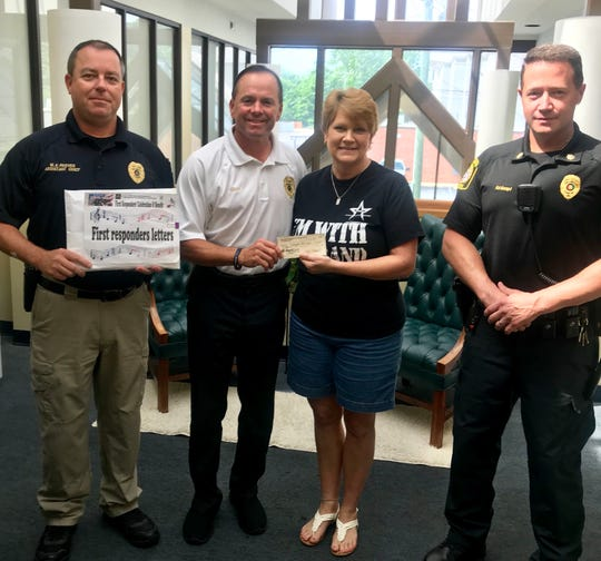 MAMA president Alesia Gilliland presents a check to Chief Greg Benton and a couple of their officers at the Wetumpka Police Department.