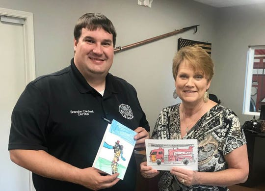 Capt. Brandon Cardwell and MAMA president Alesia Gilliland hold children's drawings of firefighters. A check for $700 was donated last week to the Elmore County Volunteer Firefighter's Association.