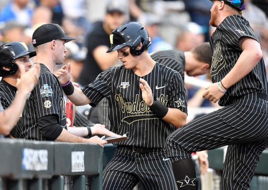Vanderbilt's Pat DeMarco (18) is congratulated after scoring on a Michigan wild pitch in Game 2 of the College World Series championship series on Tuesday.
