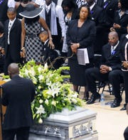 Mechelle McNair, second from left, wife of the late Steve McNair, stands with two of her sons during the funeral service for her husband in Hattiesburg, Miss. July 11, 2009. At right is McNair's brother, Fred McNair, and second from right is McNair's mother, Lucille McNair.