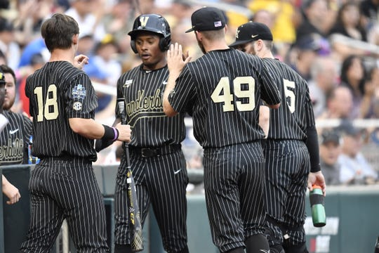 Vanderbilt's Harrison Ray (2) is congratulated after scoring in the fifth inning against Michigan in Game 2 of the College World Series championship series on Tuesday.