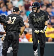 Vanderbilt catcher Philip Clarke (5) celebrates his home run with outfielder Walker Grisanti (17) in the top of the seventh inning to make the score 4-0 over Michigan in the 2019 NCAA Men's College World Series Finals at TD Ameritrade Park  Tuesday, June 25, 2019, in Omaha, Neb.