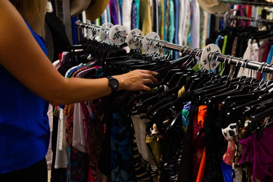 Jennifer Holderman sorts through clothing at the Twice as Nice consignment shop in Naples on Wednesday, June 26, 2019. Holderman has worked at this location for 9 months while preparing to open her own consignment shop next door.