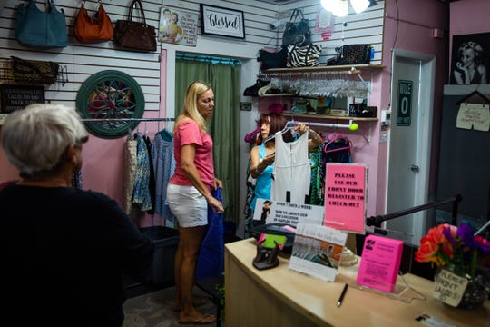 Joan Migal, left, and Coty Kjelgaard, right, discuss items brought in by a customer at the Twice as Nice consignment shop in Naples on Wednesday, June 26, 2019. Like most consignment shops, Twice as Nice re-sells used clothing, providing the former owners with a portion of the proceeds.