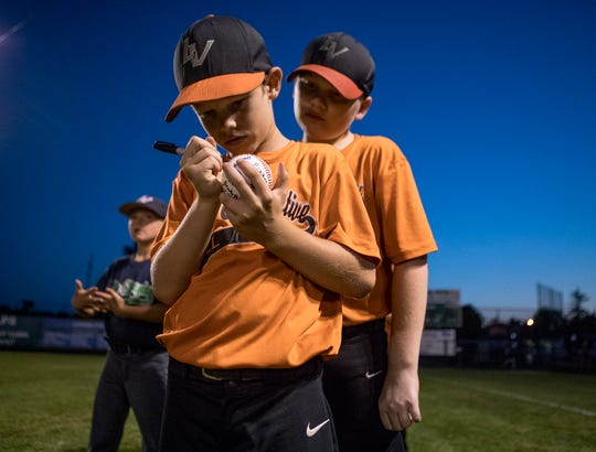 Brody Sforza signs the game ball Tuesday night at Mound City after his team, Licking Valley Energy Cooperative, won the Licking County Shrine Tournament Farm Division title.