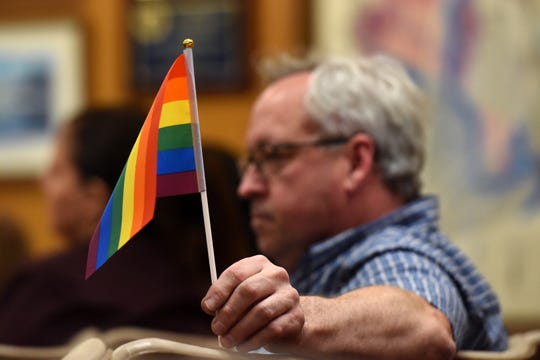 During a Hackensack City Council meeting Mayor John Labrosse, not pictured, reads a statement addressing the controversy surrounding the Hackensack Board of Education Trustee Frances Cogelja. Cogelja made disparaging comments about LGBTQ education. Labrosse accepted an apology from Cogelja. Hackensack resident Charles Avallone holds a Pride flag.