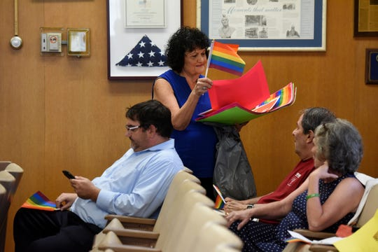 During a Hackensack City Council meeting Mayor John Labrosse, not pictured, read a statement addressing the controversy surrounding the Hackensack Board of Education Trustee Frances Cogelja. Cogelja made disparaging comments about LGBTQ education. Labrosse accepted an apology from Cogelja. Hackensack resident Kathleen Salvo hands out Pride flags before the meeting.