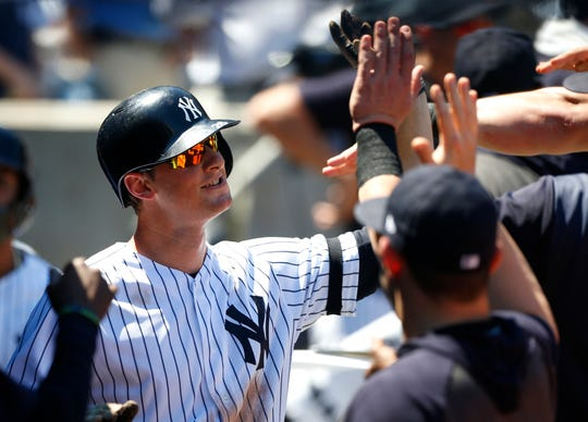 New York Yankees third baseman DJ LeMahieu (26) celebrates in the dugout after hitting a home run against the Toronto Blue Jays in the fourth inning at Yankee Stadium.