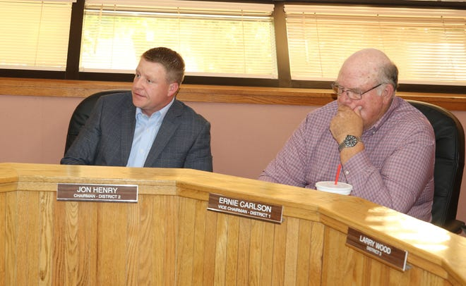 Jon Henry, chairperson of the Eddy County Board of Commissioners (left) and District 1 Commissioner Ernie Carlson talk business during the June 25 commission meeting.