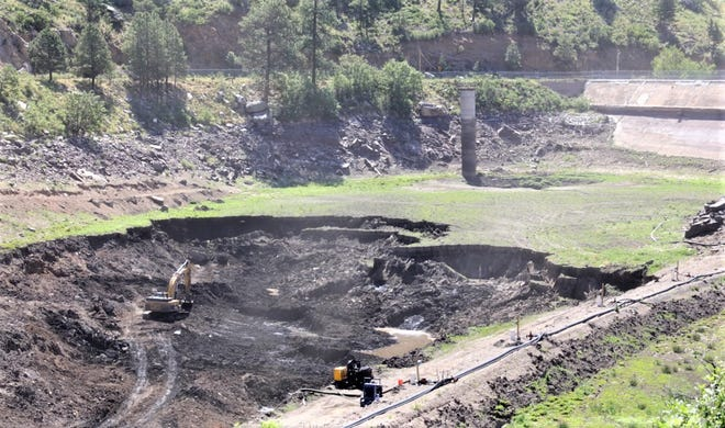 Excavation is nearing the exposed dam at Bonito Lake, seen at top right.