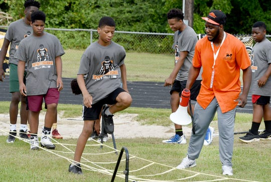 Young football players train in agility drills at the start of the annual Devery Henderson Football Camp held Saturday at Opelousas High School.