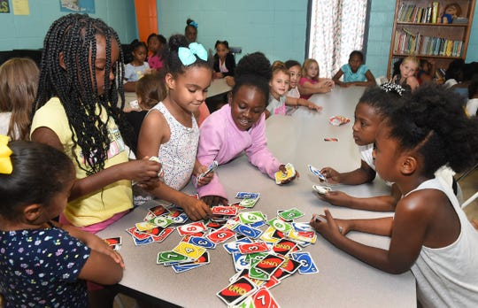 Opelousas Boys and Girls Club members engage in a game of Uno while attending the summer session of fun and educational events the club offers.
