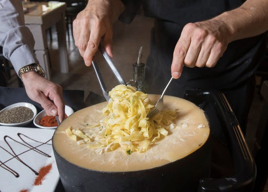 Manager Vincent Langevin, left, garnishes the plate as owner David Langevin mixes pasta in a 25-pound wheel of Parmesan as they prepares a dish of Frutti di Mare Parmigiano tableside at the new La Trattoria restaurant in Pensacola on Wednesday.