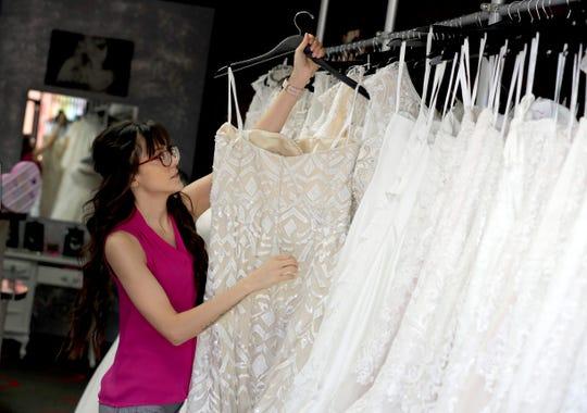Assistant manager Brooke Hernandez hangs wedding gowns Friday, June 21, 2019, at Strut Bridal Shop in Tempe.