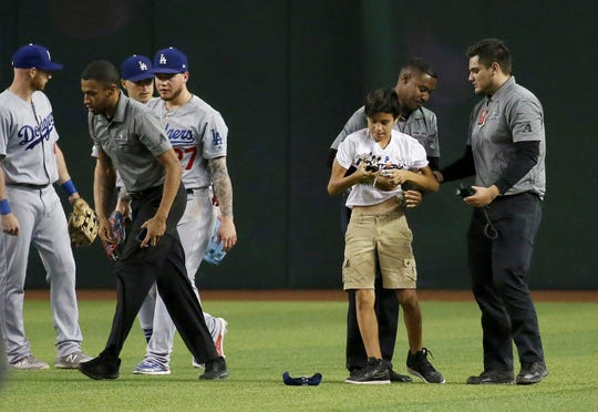 Members of Chase Field security detain a spectator who ran on the field as Los Angeles Dodgers' Kyle Garlick, left, Enrique Hernandez, third from left, and Alex Verdugo, fourth from left, stand nearby after the final out of the team's baseball game against the Arizona Diamondbacks on Tuesday, June 25, 2019, in Phoenix. The Dodgers won 3-2.
