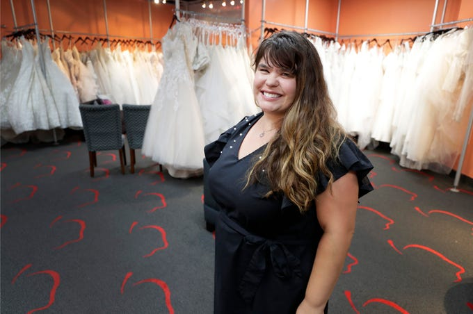In this Friday, June 21, 2019, photo Ann Campeau, owner of Strut Bridal, stands in her shop in Tempe, Ariz. Cut-rate prices on websites that sell wedding dresses direct from China put pressure on Campeau, who owns four bridal shops in California and Arizona. She has had customers come in after seeing low-end gowns online and expecting to get a dress at a similar price.