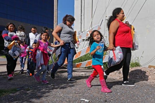 Familias de migrantes caminan tras ser procesadas en la Estación Central de Autobuses de McAllen, Texas.