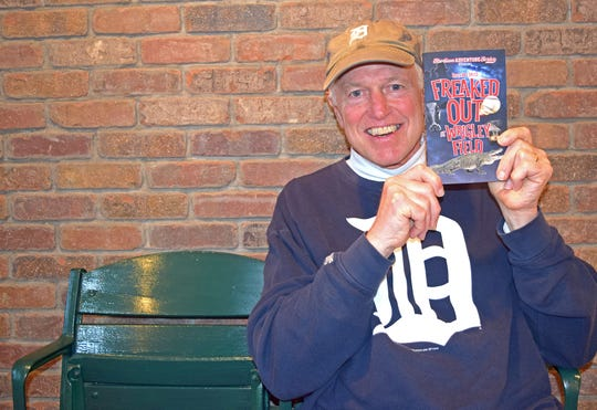"Longtime Port Clinton tourist Roger D. Hess of Michigan holds his book, ""Freaked Out at Wrigley Field"" which is set in Port Clinton."