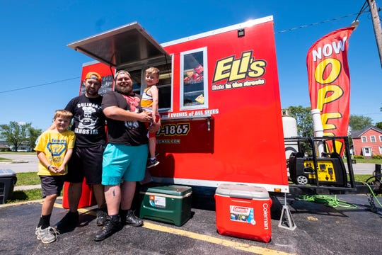 Gary Lokers, owner of Eli's Eats in the Streets, left of center, poses with his son Eli, 6, left, and George Emerson, right of center, and his son Wyatt, 5, Tuesday, June 25, 2019 at Ryan's Market in Port Huron.