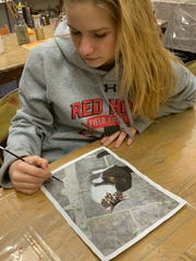 Red Hook High School sophomore Alette van Dijk works on a watercolor of a cat at Imagination Station in Red Hook.