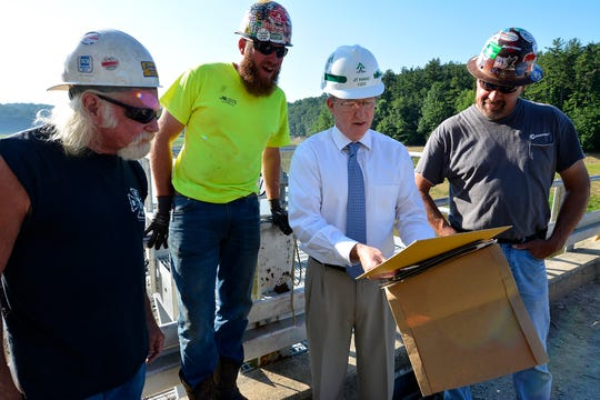 JT Hand, chief operating officer of York Water Company, center, shows workers historic photos of the Lake Williams dam construction from 106 years ago, Wednesday, June 26, 2019. John A. Pavoncello photo