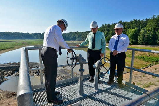 York Water Company President Jeffery Hines, left, Mark Snyder, VP of Engineering, and Marty Strine, manager of operations, test the new manual valve system for opening and closing water flow through Lake Williams dam, Wednesday, June 26, 2019. John A. Pavoncello photo