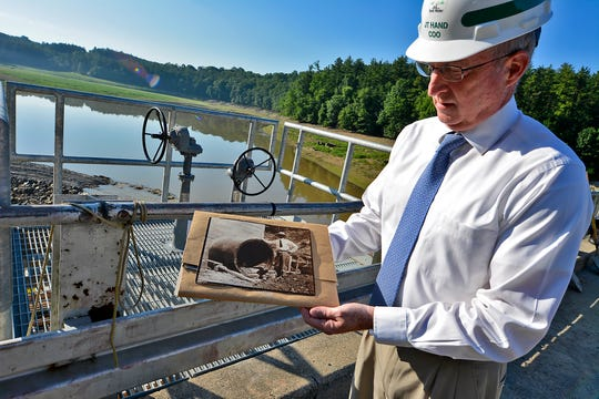 JT Hand, chief operating officer of York Water Company, holds a photo of the Lake Williams dam from 106 years ago, Wednesday, June 26, 2019. A construction project to fix the original pipe shown in the photo is nearing completion.