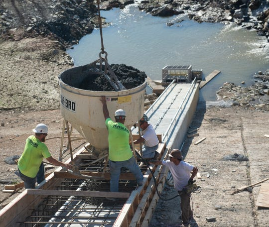 A Kinsley Construction crew pours concrete over a pipeline connecting the valves at Lake Williams dam on Wednesday. Once concrete is poured, Lake Williams will be refilled after being drained since last fall to allow for work on the dam.
