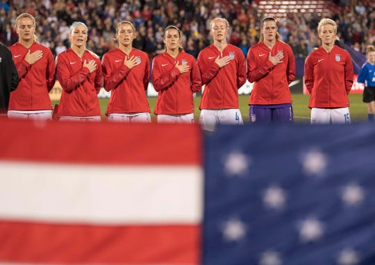 In this Oct 14, 2018, file photo, members of the U.S. women's national soccer team except Megan Rapinoe, right, sing the national anthem before a game against Jamaica in a 2018 CONCACAF Women's Championship soccer match at Toyota Stadium in Texas. Rapinoe, a native of Palo Cedro, California, doesn't sing the anthem nor salute the flag as part of a protest.