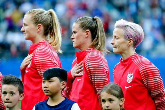 U.S. Women's National Team midfielder Sam Mewis, left, goalkeeper Alyssa Naeher and forward Megan Rapinoe stand for the National Anthem before Group F play against the Thailand in the FIFA Women's World Cup France 2019 at Stade Auguste-Delaune on June 11, 2019.
