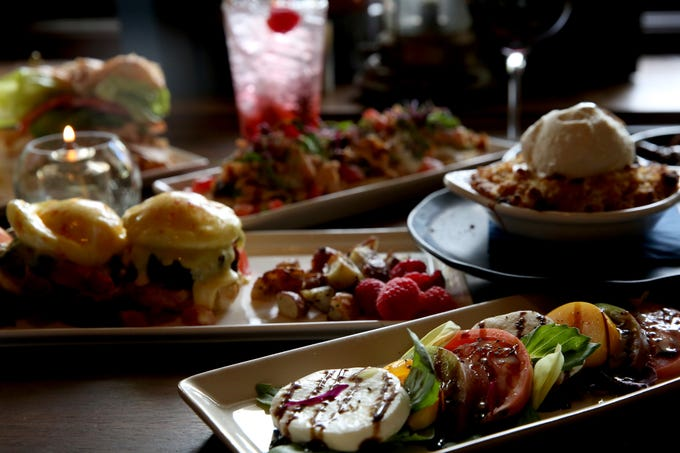 "From front, tomatoes stacked with basil, fresh mozzarella and a balsamic reduction, the Pork Belly Benedict, the ""Famous White's Restaurant Apple Crisp"" topped with a scoop of Dolce Mama's bourbon vanilla bean ice cream, avocado toast with smoked salmon and eggs on 10 grain bread, a Shirley Temple, and the avocado turkey sandwich with roast turkey breast, avocado, lettuce and tomato on a croissant with fries, at Whiskey Brown's Farmhouse Kitchen at the Salem Golf Club on June 25, 2019."