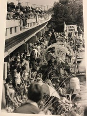 A big crowd of spectators and participants crowd the Concho River and Bell Street Bridge in anticipation of the River Rat Raft Race during Fiesta Del Concho in 1985.