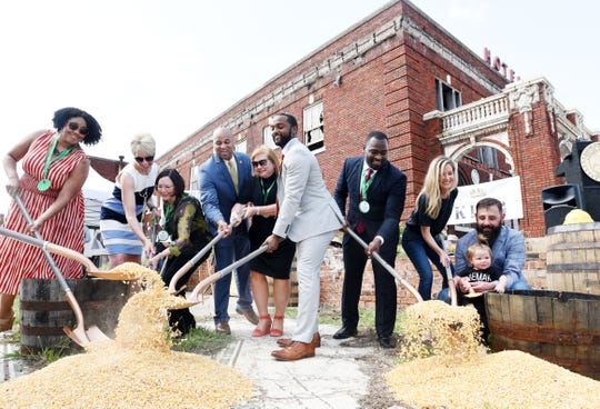 City leaders, Mayor Adrian Perkins (center) and business owners Andrew Larson and Lindsey Pennington (right) participate in the groundbreaking celebration for Every Man a King Distilling and the Revenir restaurant Wednesday afternoon, June 26, 2019.