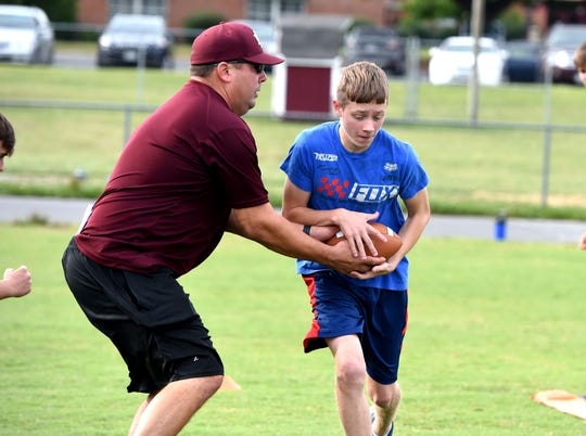 Stuarts Draft assistant coach Josh Podgorski works with the running backs at the Stuarts Draft youth football camp Tuesday night.