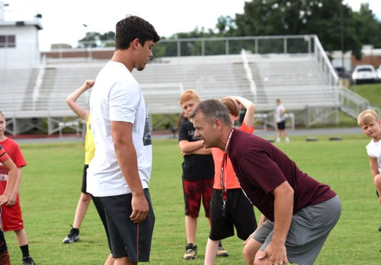 Stuarts Draft coach Nathan Floyd (right) and Kasey Branch demonstrate techniques to the youth players during a football camp last summer.