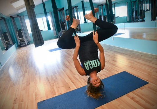 Laura Brand demonstrates a pose used in aerial yoga classes Tuesday, June 25, 2019, at Barre Bodies fitness studio in Sartell.