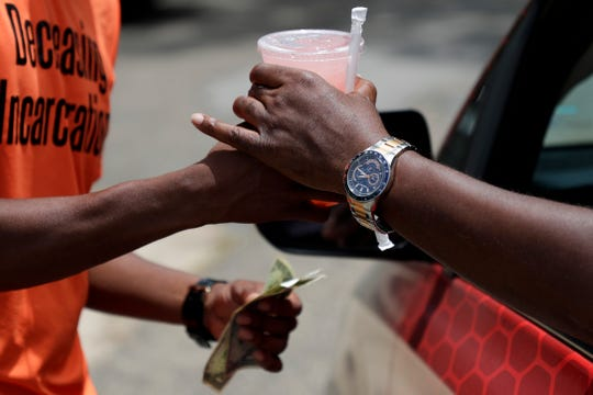 Demetrius Murray, co-owner of Gurlie's Lemonade, exchanges a cup of the pink drink for $3 from a customer that pulled over to make the purchase on Tharpe Street Tuesday, June 25, 2019.