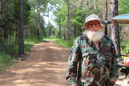 John Wilkerson, 70-year-old steward of the Glendale Memorial Nature Preserve, poses for a photo in one of the few dirt roads he maintains on the 350-acre property. Some of the roads are covered with old carpeting to prevent erosion.